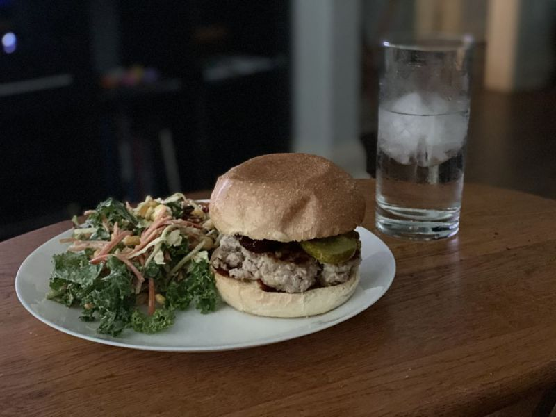 A burger and salad on a white plate next to a glass of water on a wooden surface.